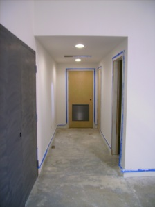 Hallway to bathrooms, primed and ready for paint.